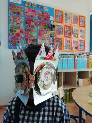 Criança com máscara tendo como fundo trabalhos que serviram de inspiração (Kandinsky)