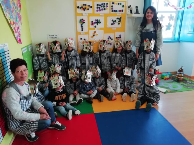 Fotografia dos alunos na sala de aula com outros trabalhos com materiais reciclados (a turma tem 24 alunos e todos têm uma máscara que levarão para casa)