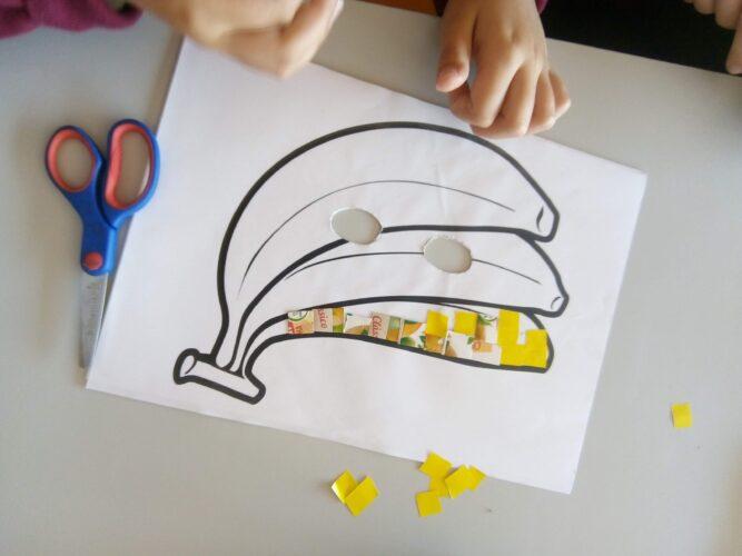Fase de construção das máscaras<br/>Os alunos colaram os quadradinhos de acordo com as respetivas cores dos frutos, na máscara.