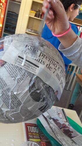 AS tiras de papel de jornal foram coladas com cola branca num balão de borracha