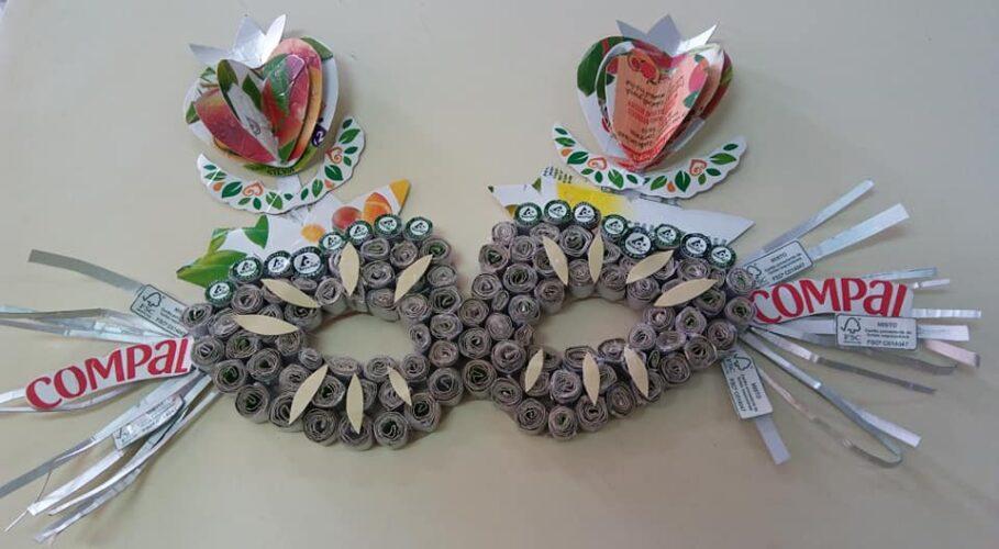 Aplicação de dois morangos e de outros elementos elaborados com recurso à reutilização de embalagens Compal/Tetra Pak para decoração da máscara.