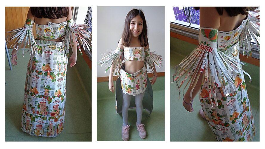 Visualização da máscara (atrás) na modelo/ aluna do 3º ano de escolaridade (top, saia, braçadeiras e colar).
