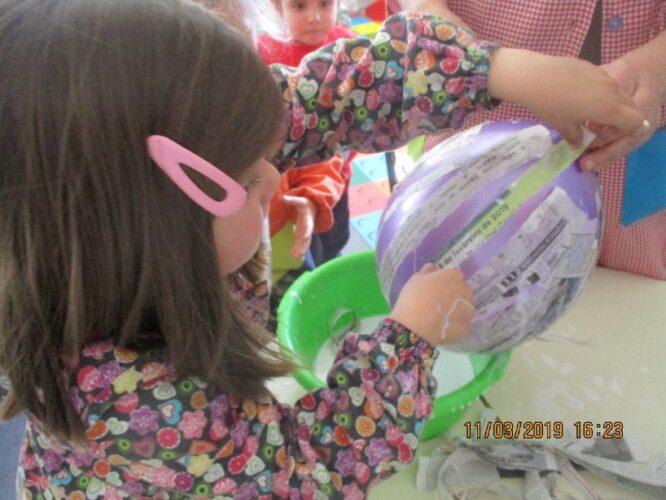 Envolver o balão com as tiras de papel molhadas em cola