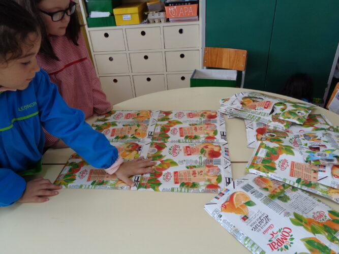 As crianças do jardim de infância ajudaram a colar as embalagens para se fazer o modelo de máscara.