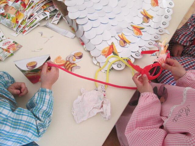 Execução de uma máscara com os frutos recortados colados nos óculos de plástico usados na casinha das bonecas e uma carteira feita com a embalagem Tetra Pak Compal e alça de trapilho.