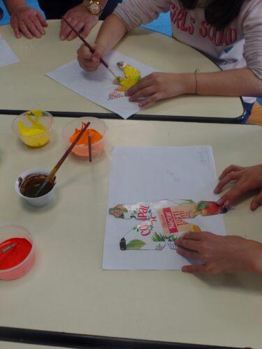 Crianças a pintar os frutos com tintas acrílicas sobre as embalagens de sumo da marca Compal.