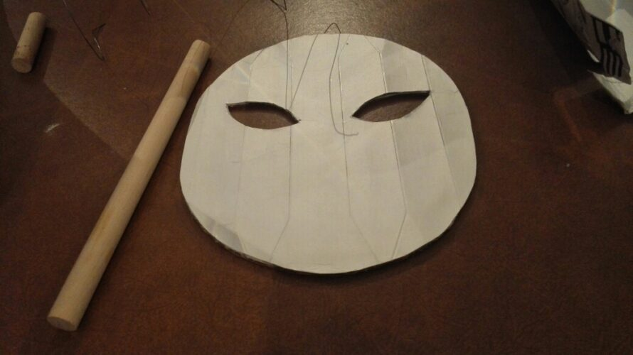 Parte frontal da máscara feita com embalagem Tetra Park da marca Compal e cilindro de madeira para suporte da máscara.