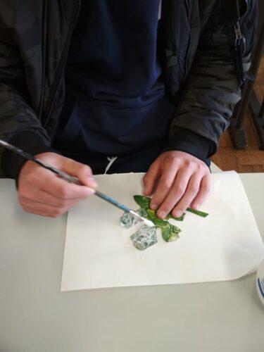 Colagem dos recortes das embalagens em suporte de cartão, com cola branca