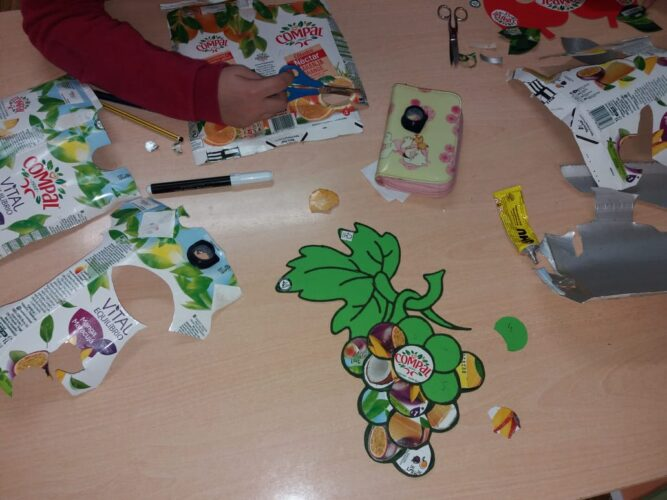 O início dos trabalhos, com a escolha dos frutos e recorte dos símbolos Tetra Pak e FSC<br/>Recorte de alguns elementos das embalagens Compal para decorar a máscara.